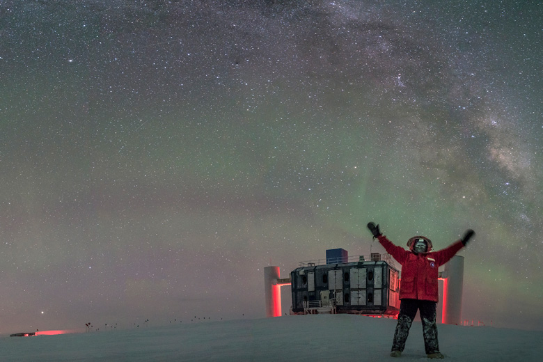 a researcher in a red polar suit in front of the IceCube lab at night with starry skies